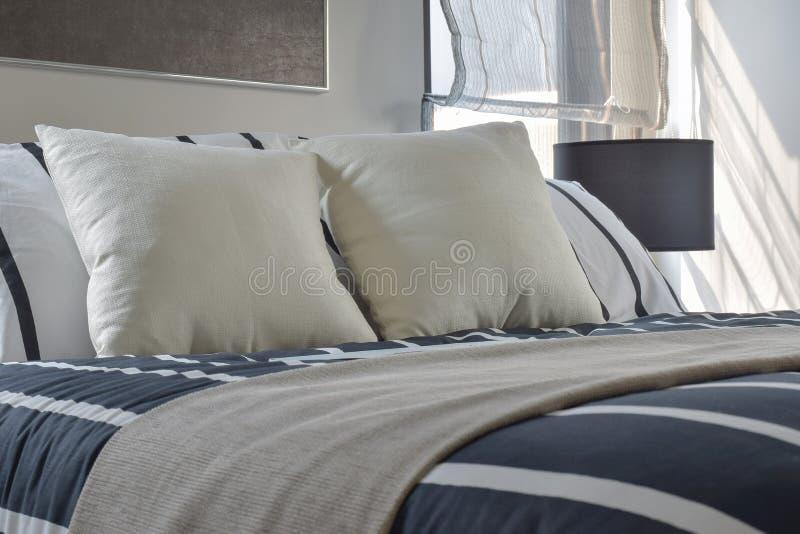 Gebroken witte en gestreepte hoofdkussens op bed met diep blauwe gestreepte deken in moderne binnenlandse stijlslaapkamer royalty-vrije stock foto's