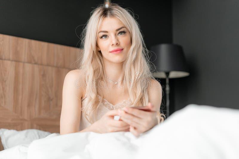 Gebruik de telefoon Controles e-mail en sociale media berichten Het jonge vrouwenkielzog omhoog, zit op comfortabel bed Ochtend i royalty-vrije stock fotografie
