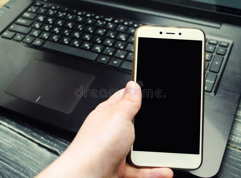 Gebruik van een mobiele telefoon met het scherm op laptop keyb royalty-vrije stock afbeelding