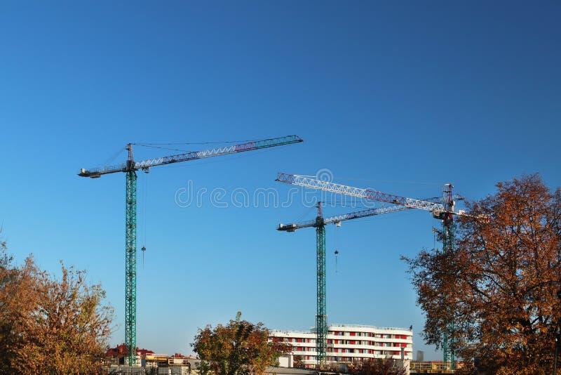 Gebruik van hoge het metaalkranen van het torenkader in bouw Panorama van de ontwikkeling van de stad tegen de blauwe hemel Het w stock afbeelding