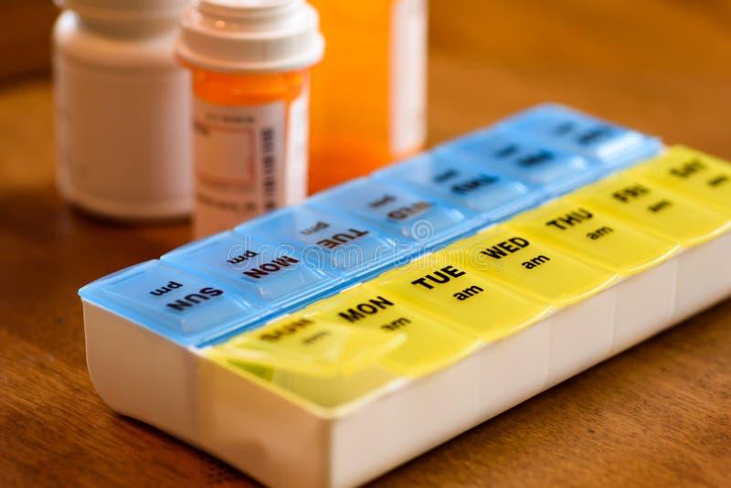 Gebruikend een pillenhouder als dagelijkse herinnering voor het nemen van medicijn royalty-vrije stock afbeeldingen