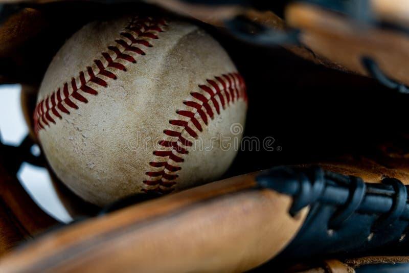 Gebruikt honkbal binnen een handschoen stock foto's