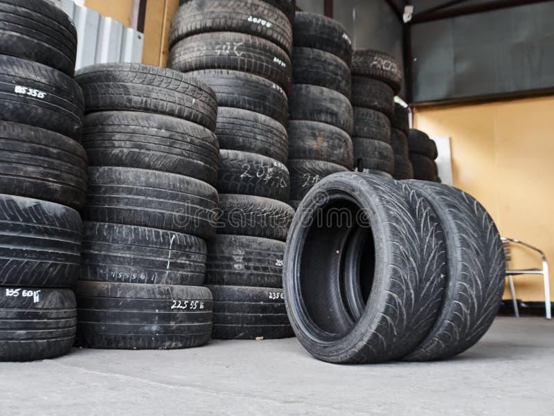 Gebruikte die autobanden in stapels bij autokerkhof worden gestapeld Oud wielen recycling en gebruik concepr stock fotografie