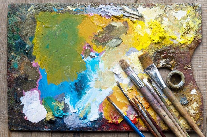 Gebruikte het kunstenaars` s palet, borstels, close-up royalty-vrije stock foto