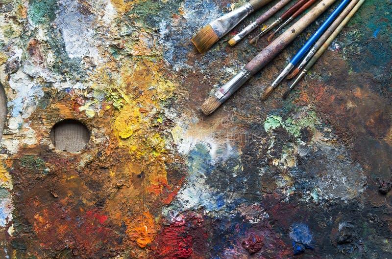 Gebruikte het kunstenaars` s palet, borstels, close-up stock afbeeldingen