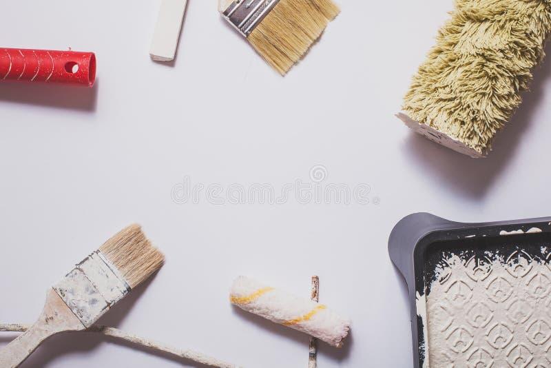 Gebruikte het schilderen hulpmiddelen met rode die handvatten in warme witte die verf worden behandeld in een samenstelling op ee stock afbeeldingen