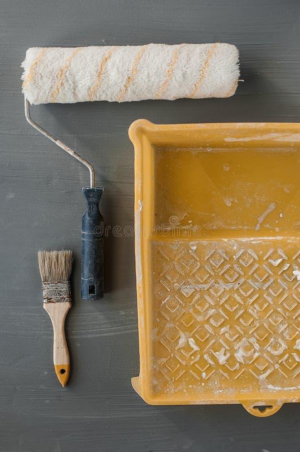 Gebruikte rol, borstel en emmer voor verf op de achtergrond stock foto's