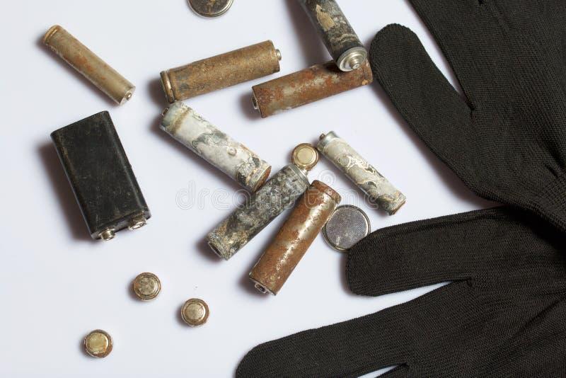 Gebruikte vinger-gekronkelde die batterijen met corrosie worden behandeld Zij liggen op een houten doos Volgende werkende handsch stock afbeelding