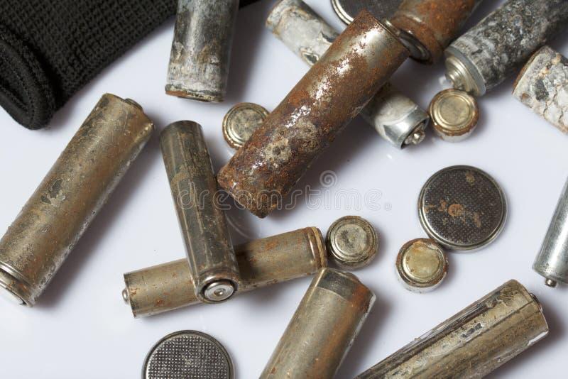 Gebruikte vinger-gekronkelde die batterijen met corrosie worden behandeld Zij liggen op een houten doos Volgende werkende handsch stock fotografie