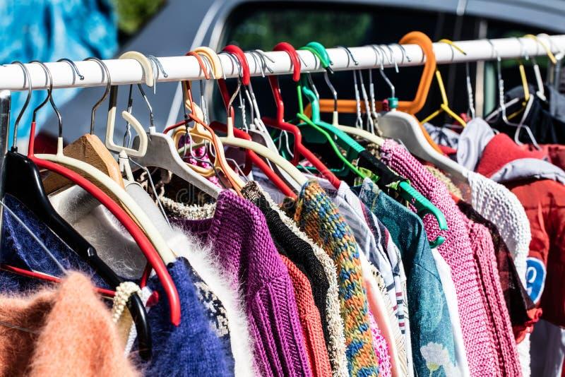 Gebruikte vrouwelijke sweaters op rek voor het opnieuw gebruiken bij vlooienmarkt stock fotografie