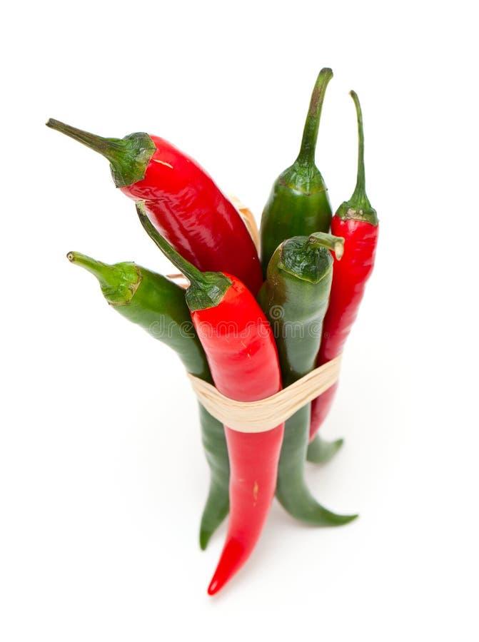Gebundene rote und grüne Pepperonis auf Weiß stockbilder