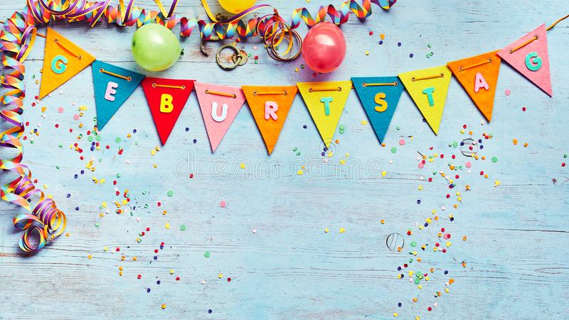 Geburtstag or Birthday party background. With streamers and balloons above a string of colorful bunting with German text and copy space below on blue wood stock photos