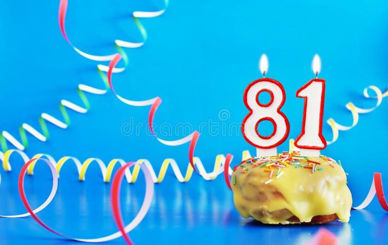 Geburtstag von achtzig einen Jahren Kleiner Kuchen mit weißer brennender Kerze in Form von Nr. 81 lizenzfreie stockbilder