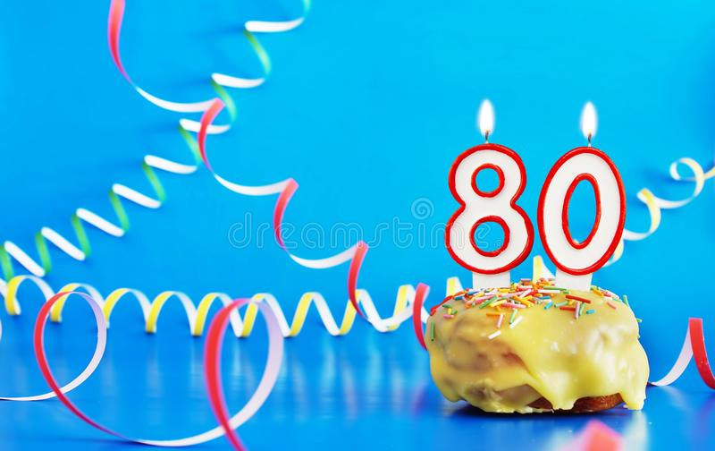 Geburtstag von achtzig Jahren Kleiner Kuchen mit weißer brennender Kerze in Form von Nr. 80 stockbild