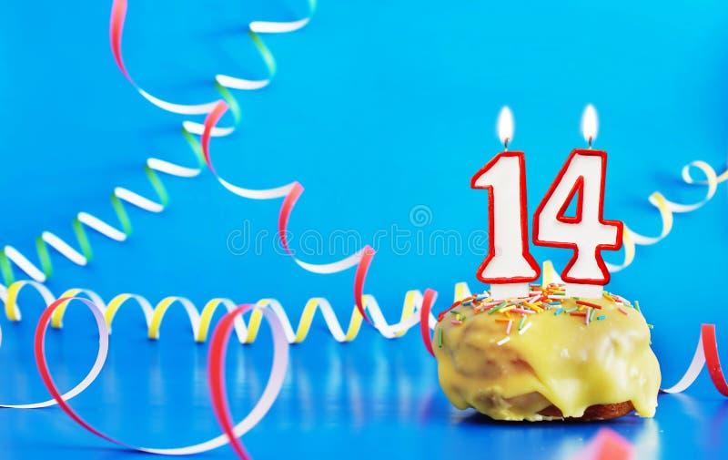 Geburtstag von vierzehn Jahren Kleiner Kuchen mit wei?er brennender Kerze in Form von Nr. 14 lizenzfreie stockbilder