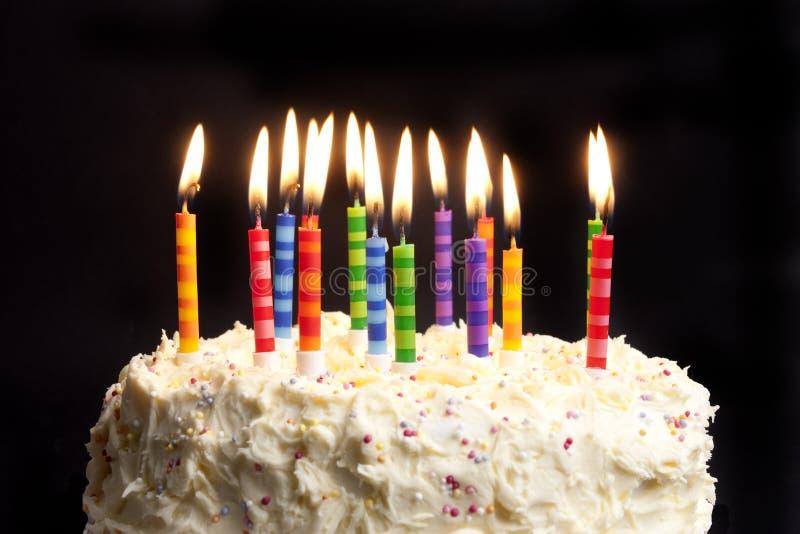 Geburtstagkuchen und -kerzen auf schwarzem Hintergrund stockfoto
