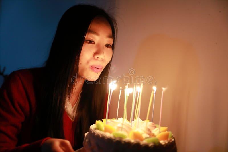 Geburtstags-Rosen-Frucht Kuchen, Frau brennen heraus die Kerzen durch lizenzfreie stockfotos