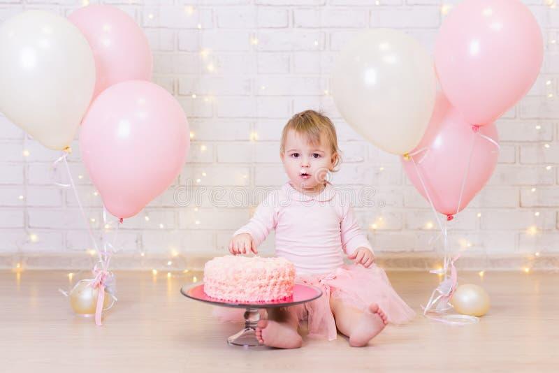 Geburtstagsfeier - glückliches kleines Mädchen mit Kuchen über Ziegelstein wa lizenzfreie stockfotografie