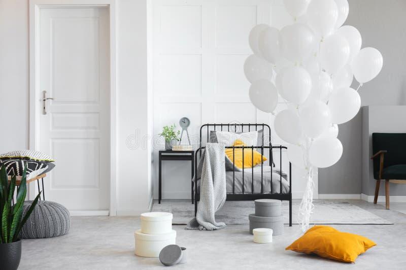 Geburtstagsfeier im weißen industriellen Schlafzimmer mit Metallbett und konkretem Boden lizenzfreie stockfotos