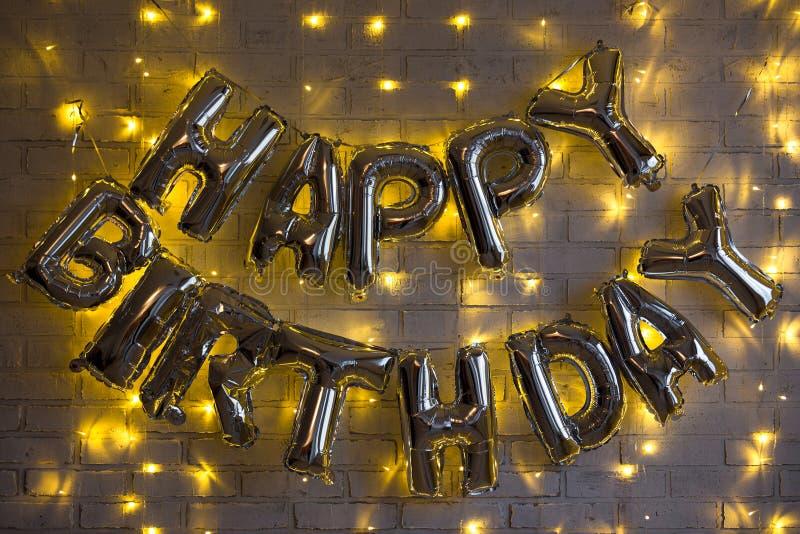 Geburtstagsfeierdekoration - alles- Gute zum Geburtstagbuchstaben lüften Ballone über Backsteinmauer mit Lichtern lizenzfreie stockfotos
