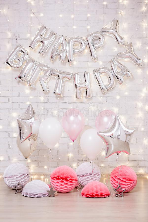 Geburtstagsfeierdekoration - alles- Gute zum Geburtstagbuchstaben lüften Ballone, Sterne und Papierbälle über Backsteinmauer mit  stockfotografie