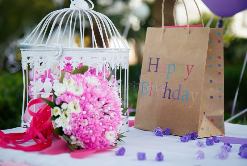 Geburtstagsfeierdekoration mit Blumen und Geschenken stockfotos