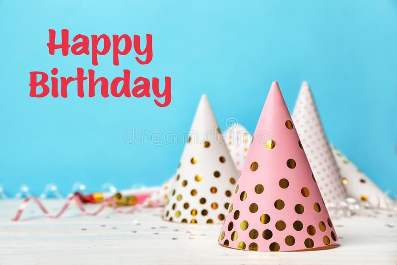 Geburtstagsfeierkappen auf Tabelle gegen Farbe stockfotos