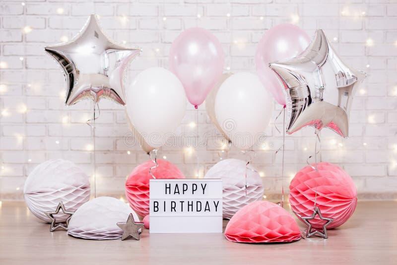Geburtstagsfeierkonzept - Abschluss oben von Luftballonen, von Papierbällen und von lightbox mit glücklichem birtday Text lizenzfreie stockbilder