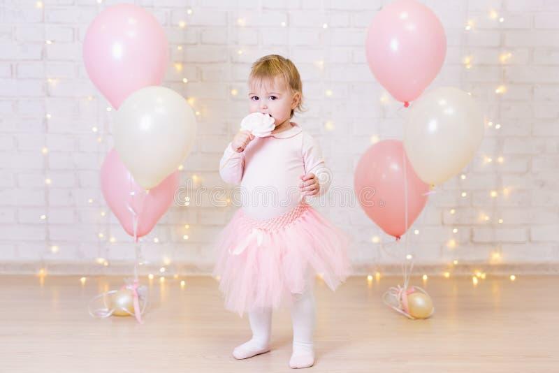 Geburtstagsfeierkonzept - kleines Mädchen, das Bonbons über Ziegelstein wa isst stockfotos