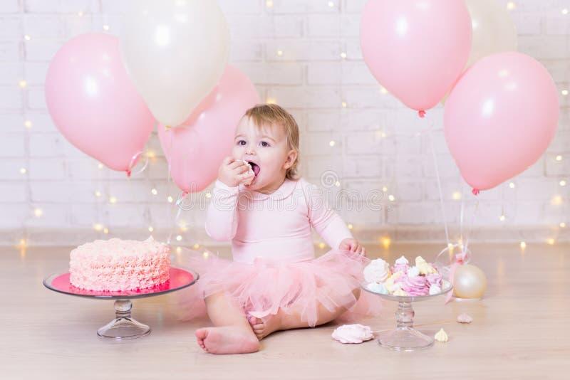 Geburtstagsfeierkonzept - lustiges kleines Mädchen, das Kuchen über bric isst lizenzfreie stockfotos
