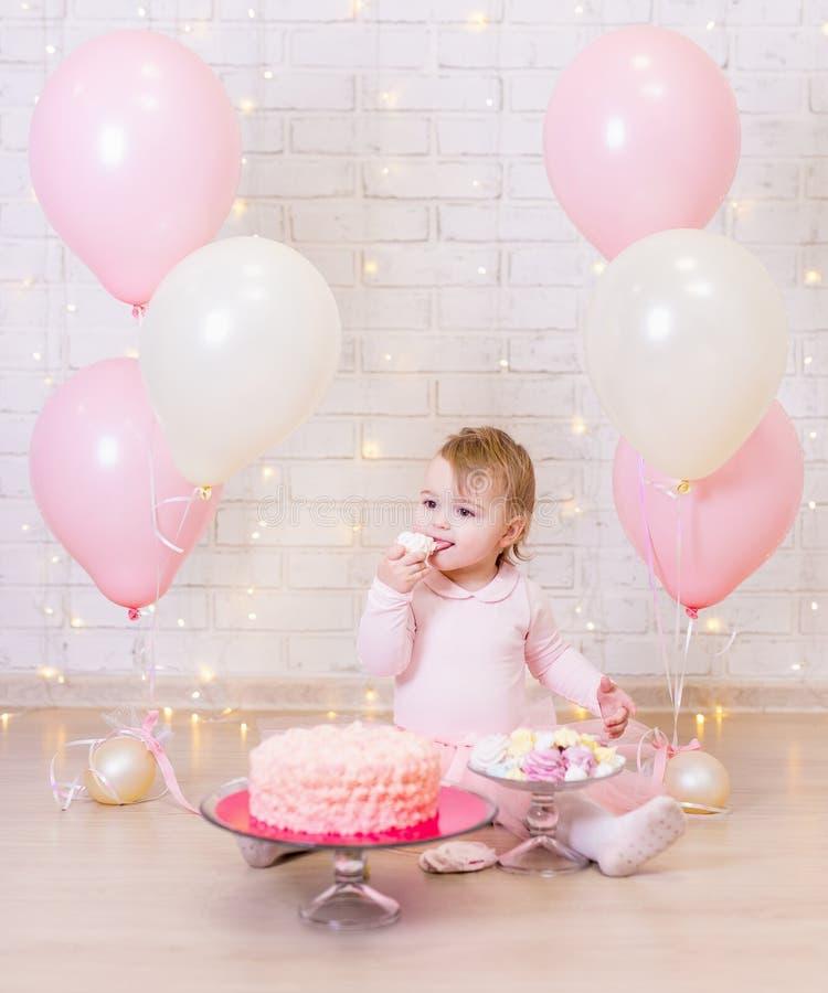 Geburtstagsfeierkonzept - nettes kleines Mädchen, das Kuchen über Ziegelstein isst stockbilder