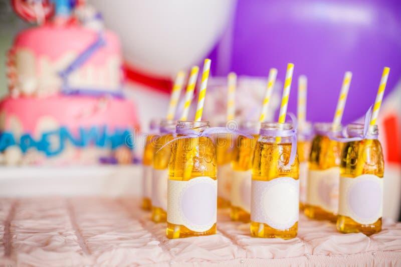 Geburtstagsfeierkonzept, Schokoriegel für Kinder Viele Flaschen Apfelsaft, spezielle Aufkleber auf den es, weißen und gelben Stro lizenzfreie stockbilder