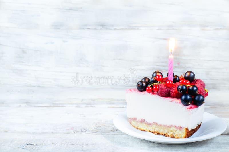Geburtstagskäsekuchen mit Kerze, Himbeeren, Rotem und Schwarzem curr stockfotografie
