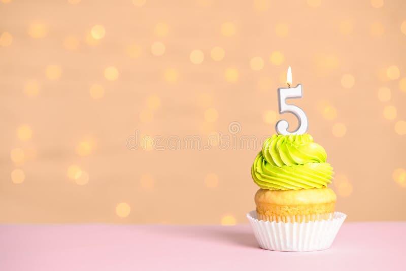 Geburtstagskleiner kuchen mit Zahl fünf Kerze an gegen festliche Lichter, Raum für Text stockfotografie