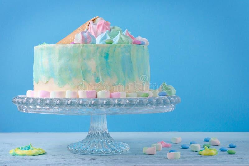 Geburtstagskuchen in den Pastellfarben auf blauem Hintergrund lizenzfreie stockbilder