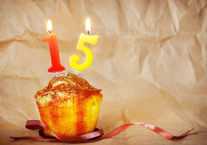 Geburtstagskuchen mit brennenden Kerzen als Nr. fünfzehn lizenzfreie stockfotos