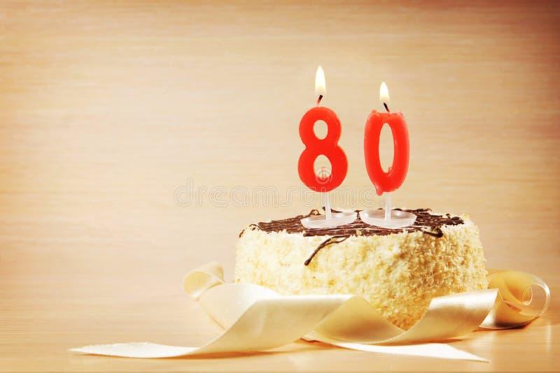 Geburtstagskuchen mit brennender Kerze als Nr. achtzig stockbilder