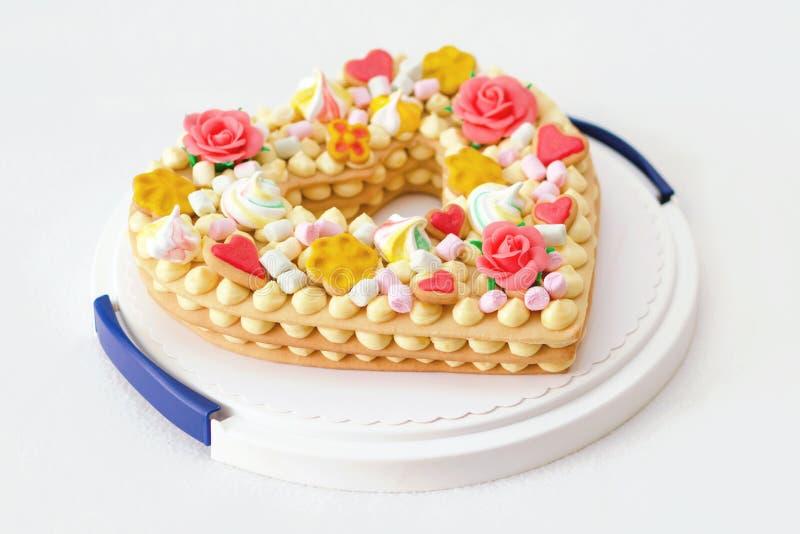 Geburtstagskuchen wie Herz mit verschiedenen Süßigkeiten stockfoto