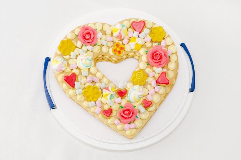 Geburtstagskuchen wie Herz mit verschiedenen Süßigkeiten, Ansicht von der Spitze lizenzfreie stockbilder