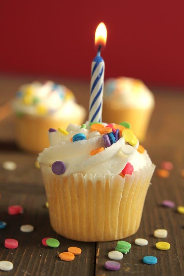 Geburtstagskupchen mit Kerze auf orangefarbenem Hintergrund lizenzfreie stockfotos
