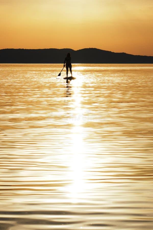 Gecentreerde zonbezinning in water en silhouet van het jonge vrouw paddelen bij zonsondergang op tribune omhoog paddleboard SUP i royalty-vrije stock foto