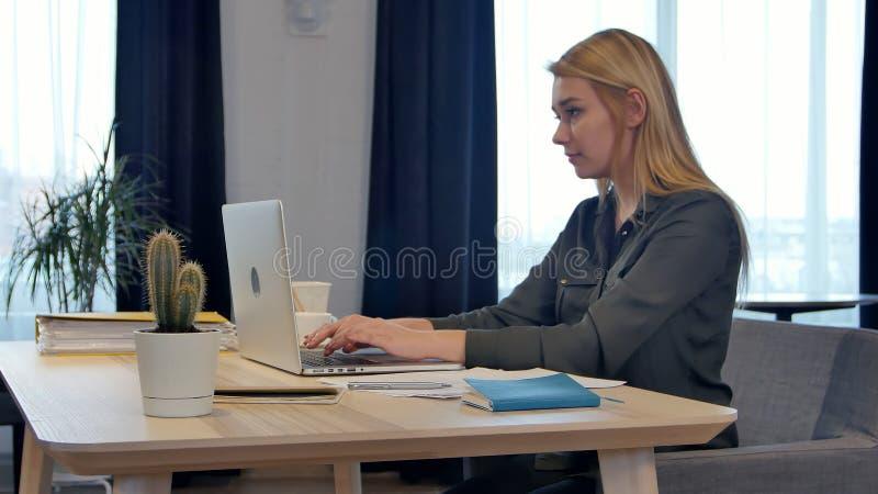Geconcentreerd bij werk, zekere jonge vrouw die in slimme vrijetijdskleding aan laptop het werken terwijl het zitten dichtbij ven stock afbeeldingen