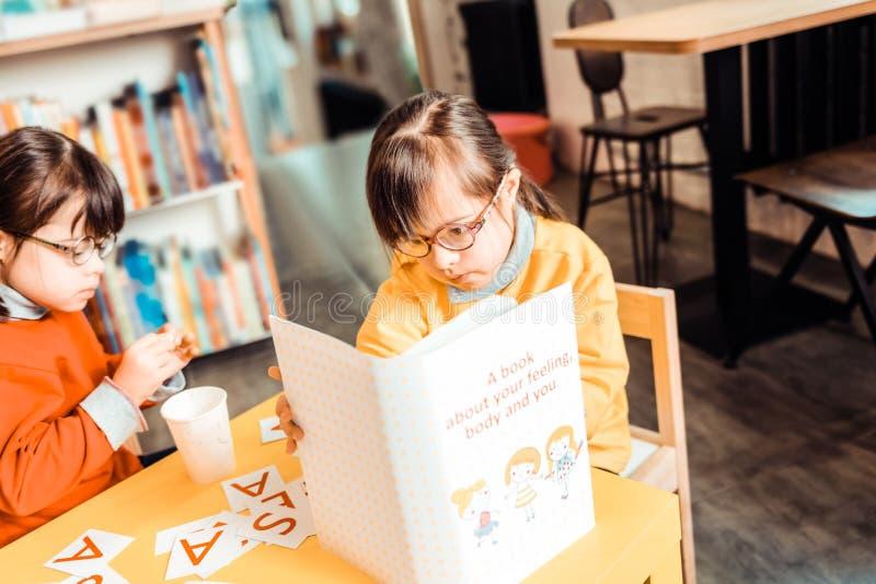 Geconcentreerd donker-haired meisje in gele sweater die aandachtig boek leest stock foto's