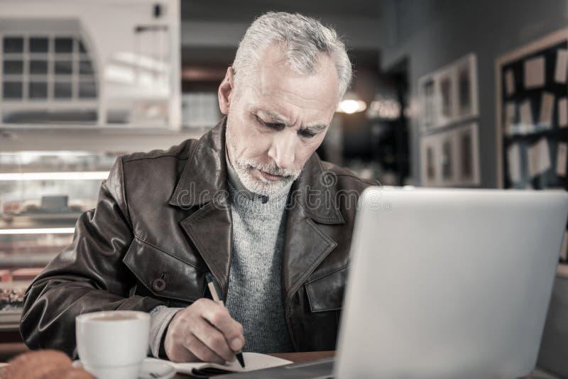 Geconcentreerd grijs-haired mannetje die nota's in voorbeeldenboek maken stock afbeelding