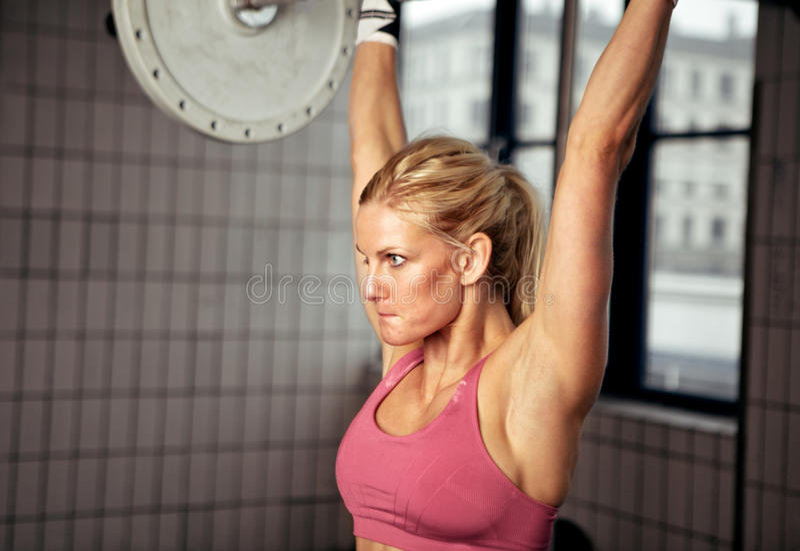 Geconcentreerd het Opheffen van de Vrouw Gewicht stock afbeeldingen