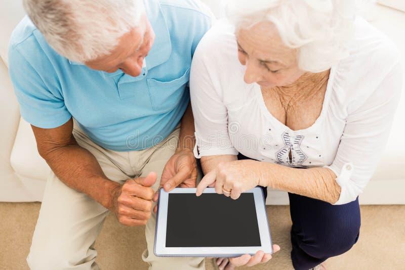 Geconcentreerd hoger paar die tablet gebruiken stock afbeeldingen