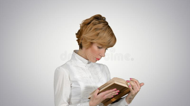 Geconcentreerd jong bedrijfsvrouwenholding en van de lezing boek op witte achtergrond stock afbeeldingen