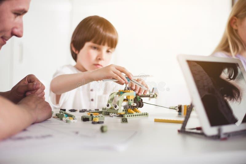 Geconcentreerd jong geitje die stuk speelgoed van aannemer maken royalty-vrije stock afbeeldingen