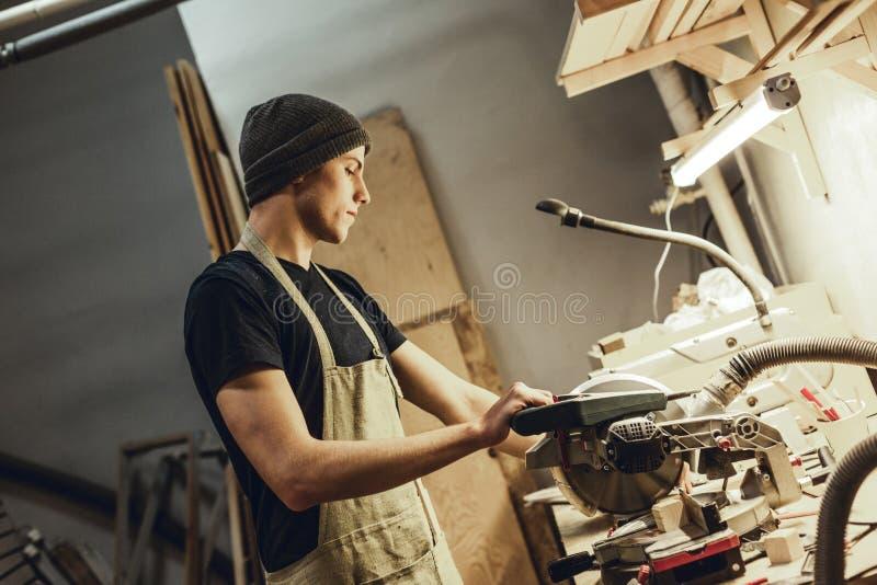 Geconcentreerd jong timmermans scherp hout stock afbeelding