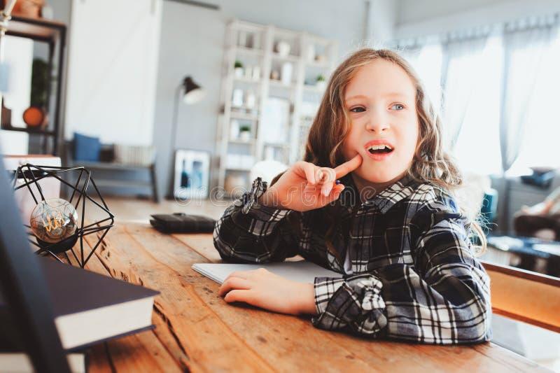 geconcentreerd kindmeisje die thuiswerk doen Nadenkend schooljong geitje die en een antwoord denken zoeken royalty-vrije stock foto's